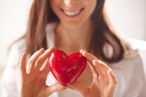 close-up-of-woman-holding-a-bright-heart_1098-2725
