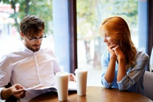 couple-with-magazine-at-coffee-shop_1098-421